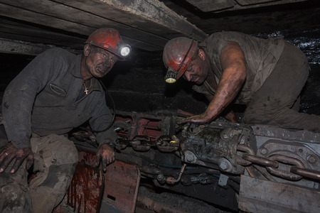 Donetsk, Ukraine - August, 16, 2013: Miners near the coal mining shearer. Mine is named Chelyuskintsev