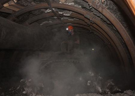 Donetsk, Ukraine - March, 14, 2014: The driver of the coal miner working in a cloud of dust in the underground mine. Mine is named Abakumov