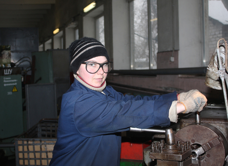 makeevka: Ukraine, Makeevka, - January, 29, 2013: The girl at the lathe turner. Plant for the production of fire extinguishers Torch