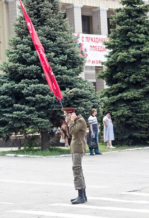 Makeevka, Ukraine - May, 9, 2012: A supporter of Communist ideology with a red flag in celebration of the anniversary of victory over fascism