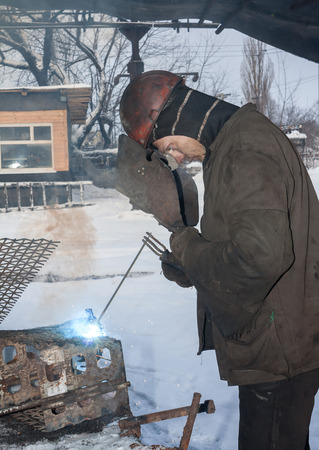 Makeevka, Ukraine - January 14, 2013: Welder working in the mine yard in winter. The mine named after Kirov