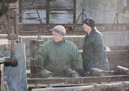 donbass: Donetsk, Ukraine - February, 20, 2013: Women work at sawing wood on the yard mine shaft Southern – Donbass №1