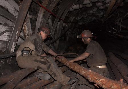 mineros: Donetsk, Ucrania - Agosto 16, 2013: Los mineros madera aserrada para la construcci�n de soporte del techo en las minas subterr�neas. Nombre Mina Chelyuskintsev