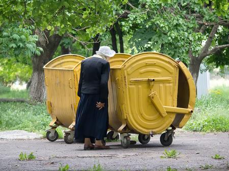 makeevka: Makeevka, Ukraine - May 29, 2015: An elderly woman near a garbage bin Editorial