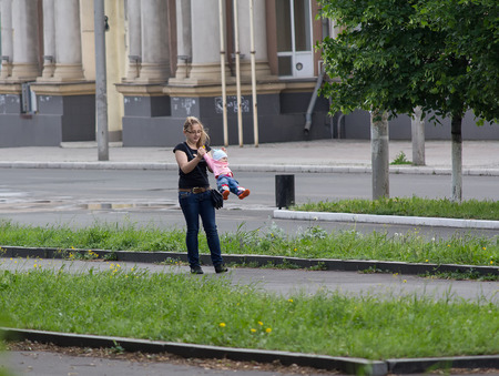 Makeevka, Ukraine - May 29, 2015: Young mother playing with her daughter on the main street of the city during the truce Editorial