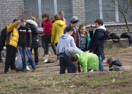 Makeevka, Ukraine - March, 26, 2015: Pupils work on landscaping the school grounds during the truce