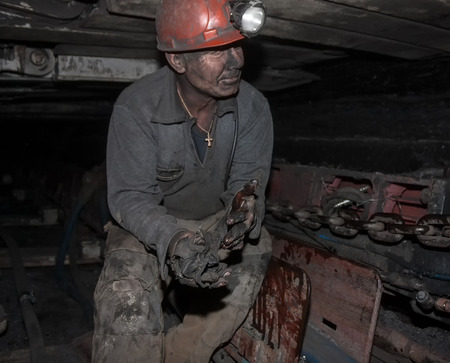COAL MINER: Donetsk, Ukraine - August, 16, 2013: Miner repairs coal mining combine. Mine name Chelyuskintsev