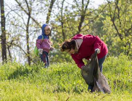 scavenge: Zugres, Ukraine - April 26 2014: Mother and daughter scavenge in the city park during the event, conducted by DTEK