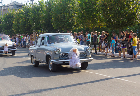 Makeevka, Ukraine - August 25, 2012: Retro cars depicting a wedding procession in the parade during the celebration of the city day Editöryel