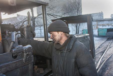 anthracite coal: Uglegorsk, Ukraine - March 12, 2014: Driver mine Uglegorskaya near trolley coal mine yard