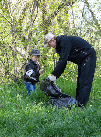 Zugres, Ukraine - April 26, 2014: Father and son clean debris from the city park during the action undertaken by DTEK