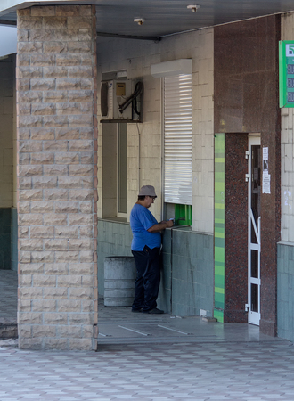 Makeevka, Ukraine - July 30, 2015: Elderly woman near an ATM at the branch of the non-working commercial bank nationalized by the authorities of the Peoples Republic of Donetsk Editorial