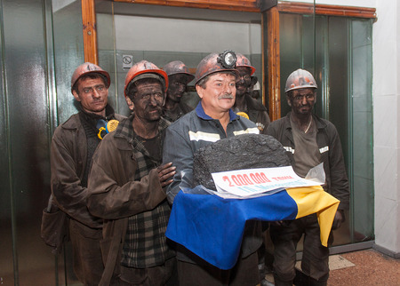 Makeevka, Ukraine - November 26, 2013: Miners with coal symbolic ingot at the ceremony in honor of 2000000 tons of coal mined in Makeevka in the current year