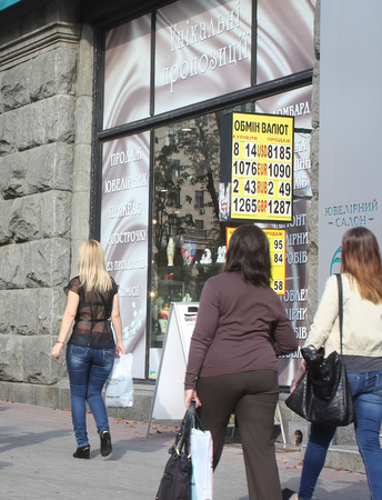 worl: Kiev, Ukraine - September 11, 2013: Passers-by looking at the billboard with the exchange rate on the street Khreshchatyk