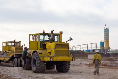 taskmaster: Krasnoarmeysk, Ukraine - October 18 2012: Tractor driver and construction worker at a construction site of a coal mine