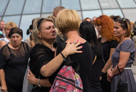 Kiev, Ukraine - September 04, 2015: Women in mourning garb express support for each other at the funeral of the deceased in the war volunteer