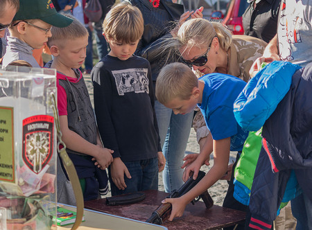 taught: Kiev, Ukraine - October 03, 2015: Children are taught to handle weapons in the street St. Andrews Descent