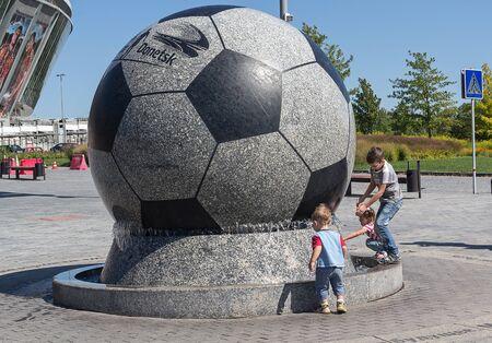 donbass: Donetsk, Ukraine - August 22, 2015: Children playing near the fountain stadium Donbass Arena during the war in eastern Ukraine Editorial