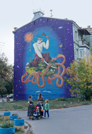 sidewalk talk: Kiev, Ukraine - September 25, 2015: Women talking in front of his house decorated with graffiti