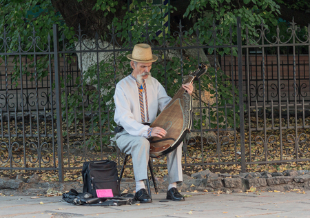 itinerant: Kiev, Ukraine - September 25, 2015: Elderly man with a national flavor plays the bandura Editorial