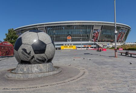 donbass: Donetsk, Ukraine - August 22, 2015: Empty during the war the stadium Donbass Arena with a sign located on its territory for humanitarian Staff Rinat Akhmetov Editorial