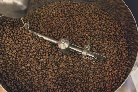hopper: Coffee beans during the roasting process inside the hopper drum type roaster
