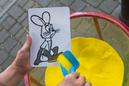 cliche: Drawing colored sand on a cliche. Educational activities for kids