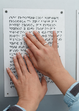 sense of sight: Her hands reading Braille table. Health and social adaptation