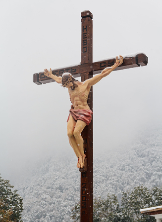 crucify: Christian cross with a crucifix in the church on a background of snow-capped mountains