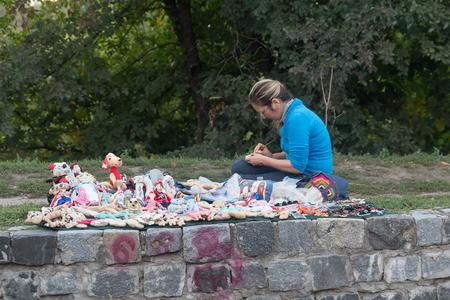 soft sell: Kiev, Ukraine - September 17, 2015: Woman makes and sells handmade dolls near the childrens playground