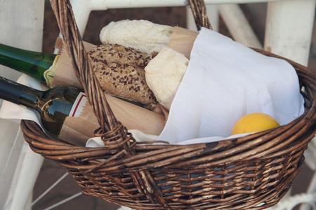 pan y vino: Bread, wine and lemon in a wicker basket. Food and beverages Foto de archivo