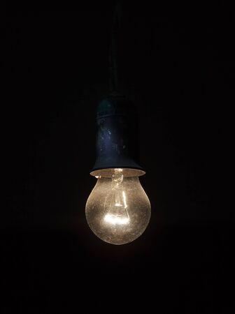 dusty: Old dusty light bulb glowing in the dark