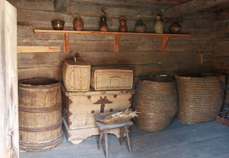 chamber pot: Chests, barrels and a shelf with dishes in the ancient peasant hut. Pirogovo, Ukraine