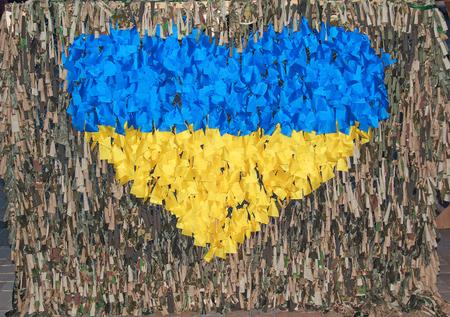 ukrainian flag: Symbol of the heart in the colors of Ukrainian flag on the woven camouflage net. Kiev