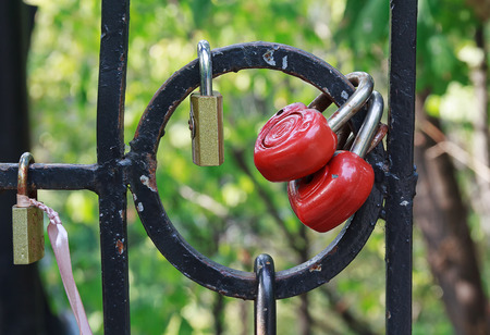 parejas romanticas: Red heart-shaped locks are hanging on the bridge lovers