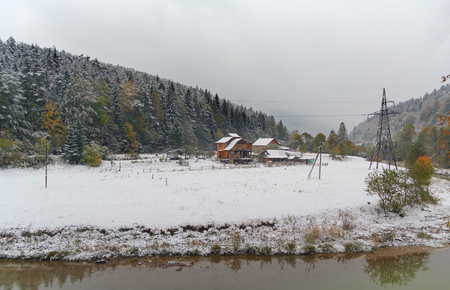 fence: Rustic farmhouse on a snowy plain, mountains in the background. Carpathian Mountains, Ukraine