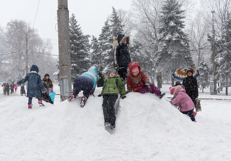 Makeevka, Ukraine - January 07, 2016: Children playing on a snowy hill on a central square in the territory controlled by the Donetsk Peoples Republic during the truce Editorial