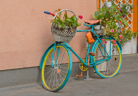Oude fiets met bloemen en een mandje van de muur. Decor