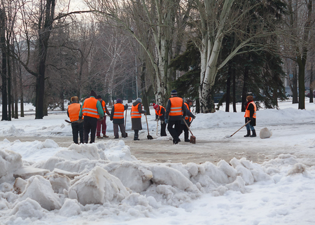 makeevka: Makeevka, Ukraine - January 14, 2016: Utility workers using shovels snow from the road clean