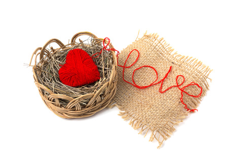 basket embroidery: Heart of yarn in a wicker basket isolated on white background Stock Photo