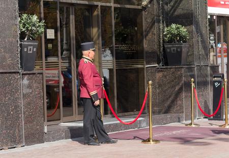 hospitality: Kiev, Ukraine - September 18, 2015: Doorman in uniform at work in the street Khreshchatyk