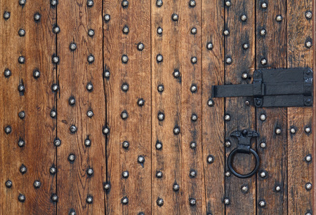metal textures: Old wooden door and a metal bolt. Backgrounds and textures Stock Photo