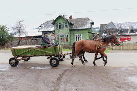 horse traction: Vorokhta, Ukraine - October 13, 2015: Local residents ride in a cart on a rural road