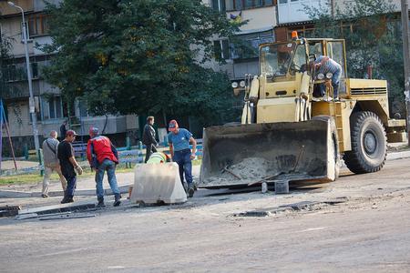 construction management: Kiev, Ukraine - September 21, 2015 : Construction management workers work to repair the road surface