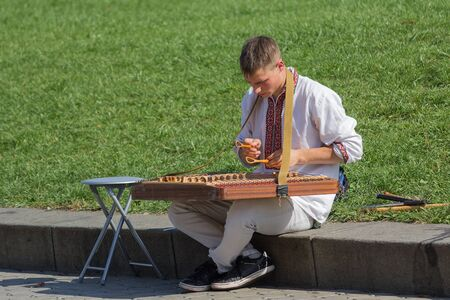 ethnic dress: Kiev, Ukraine - September 20, 2015: Male in ethnic dress playing the cymbals at Independence Square