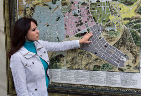 contemplates: Woman contemplates the city map on the wall. People Editorial