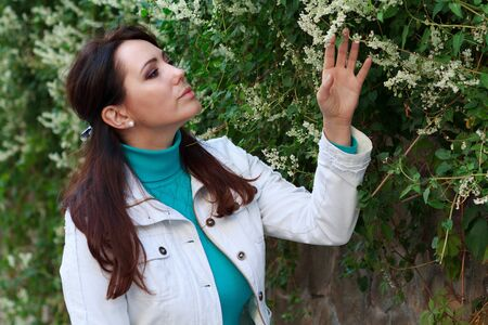 flowering plant: Beautiful lady next to a flowering plant. People Stock Photo