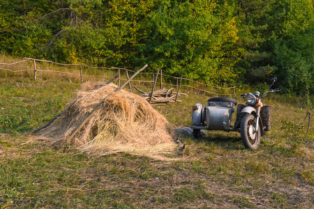 sidecar: Old motorcycle with sidecar and haystack. Countryside