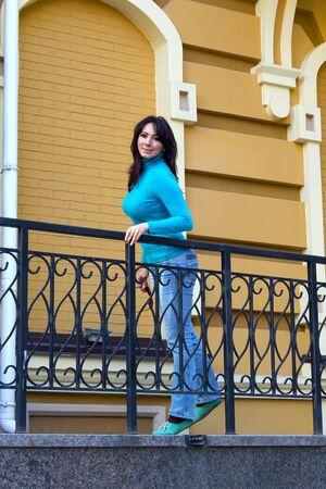 turtleneck: Beautiful girl in a blue turtleneck near the railing. People