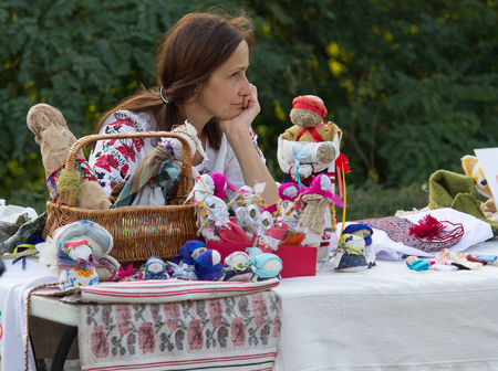 soft sell: Kiev, Ukraine - September 19, 2015: Woman in national costume sells doll its own production Editorial